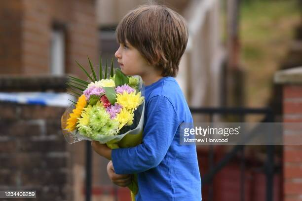 Young child brings some flowers to place as a tribute near the scene where the body of five-year-old Logan Williamson was found on August 2, 2021 in...