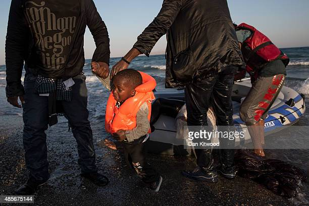 A young child called Mohammad from the Gambia is helped to shore after arriving on a beach in an inflatable dinghy on August 29 2015 in Kos Greece...