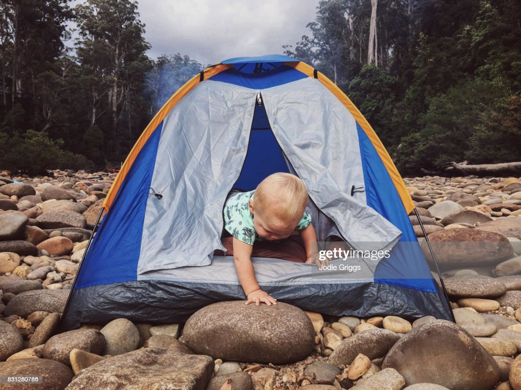 Young child climbing out of a small tent in the wilderness : Stock Photo