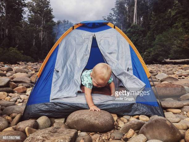 Young child climbing out of a small tent in the wilderness