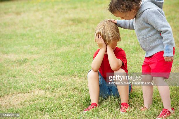 young child comforting sad young friend - consoling stock pictures, royalty-free photos & images