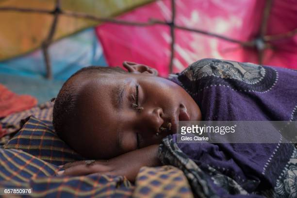 A young child covered in flies sleeps in a hot tent in a internally displaced persons camp in central Mogadishu Somalia is in the grip of an intense...