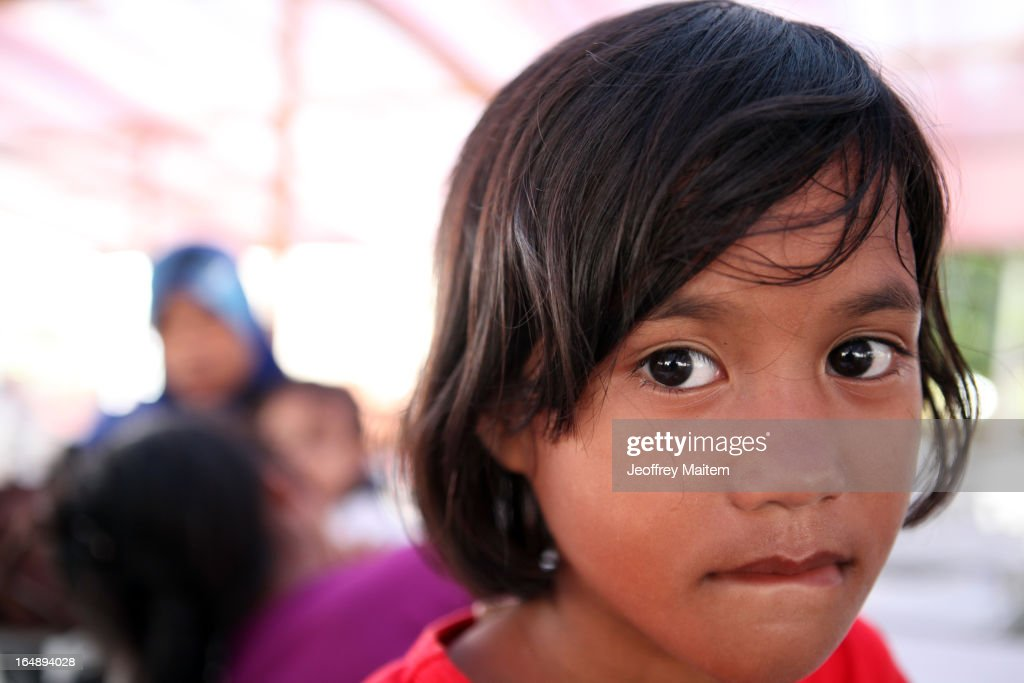 A young child, displaced by continuing armed conflict between the supporters of Philippine Muslim clan Sulu Sultan Jamalul Kiram III and Royal Malaysian Police in Sabah, Malaysia, arrives with her family at Bonggao on March 29, 2013 in Bonggao, Tawi-Tawi, Philippines. Following the insurgency in Sabah and the Malaysian government's subsequent crackdown on undocumented Filipinos, over 4000 people, mostly Filipino Muslims, have begun evacuating to the southern provinces of Basilan, Sulu, and Tawi-Tawi in the Philippines, with numbers expected to reach more than 100,000.