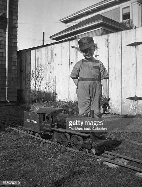 Young child dressed as a steam locomotive driver holding a pair of work gloves standing in backyard of house beside a large wooden model of a steam...