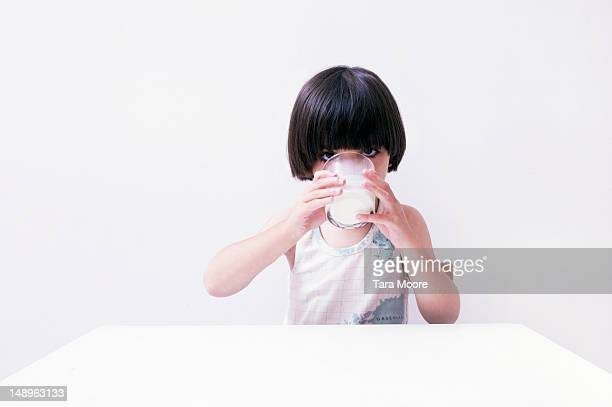 young child drinking glass of milk