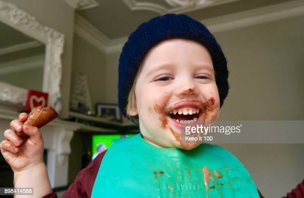 Young child eating chocolate ice cream and laughing