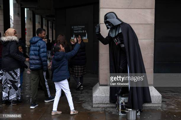 A young child gives a hifive to a man dressed as the Star Wars character Darth Vader outside the Houses of Parliament on February 18 2019 in London...