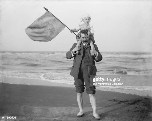 Young child holding a flag on top of the shoulders of a man at sandy beach as they celebrate Queen Victoria's Diamond Jubilee of 1897