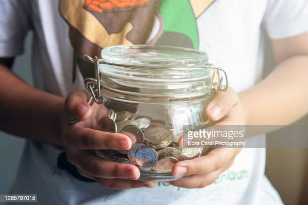 young child holding coins jar - charity benefit stock pictures, royalty-free photos & images