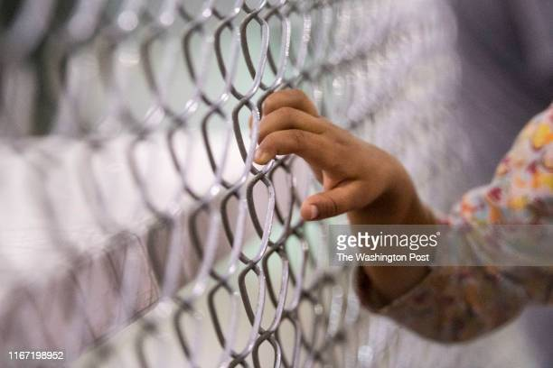 Young child holds onto a fence in the US Border Patrol Central Processing Center in McAllen, Texas on August 12, 2019. Border Patrol officials said...