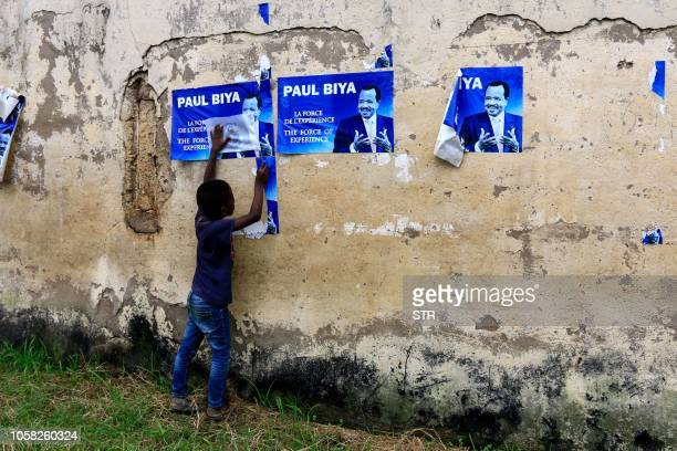 Young child holds posters of Cameroonian President Paul Biya on a wall in Yaoundé on November 6, 2018. - Cameroon's 85-year-old President Paul Biya...