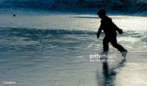 Young child ice skating at sunset