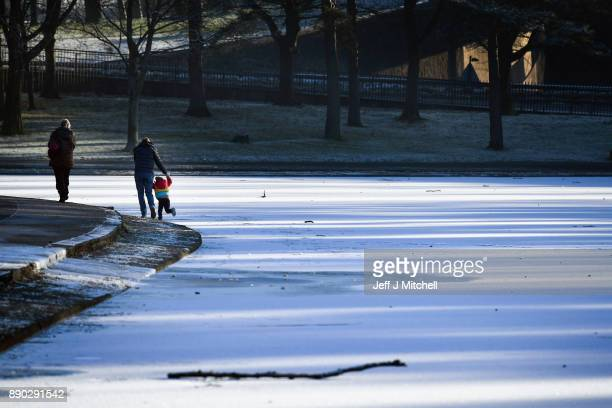 A young child is held by an adult as he enjoys walking on a frozen pond in Victoria Park on December 11 2017 in Glasgow Scotland Scotland is enduring...