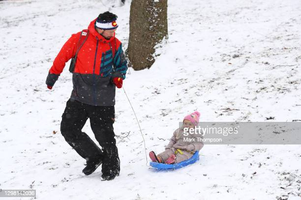 Young child is pulled on a sledge on January 24, 2021 in Northampton, England. Parts of the country saw snow and icy conditions as arctic air caused...