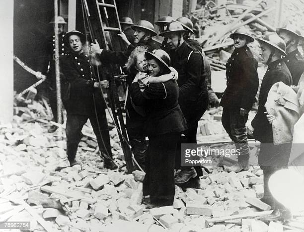 War and Conflict World War Two London England The Blitz Circa 1940 A young child is rescued by an air raid warden following a bombing raid