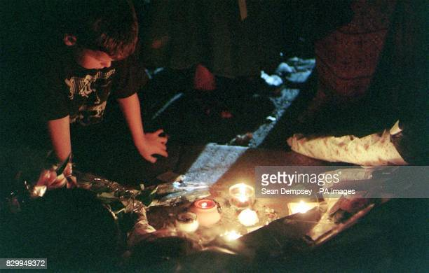 Young child kneels to look at candles placed in remembrance of Diana Princess of Wales outside St James's Palace in London this evening, . Photo by...