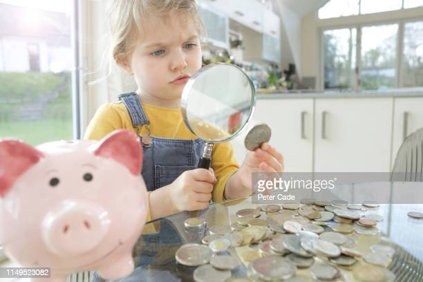 Young child looking at coins with magnifying glass next to piggy bank