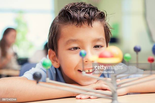 Young child looking at solar system kit in science class