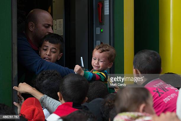 A young child looks distressed as migrants board a train in Keleti station after it was reopened this morning in central Budapest on September 3 2015...