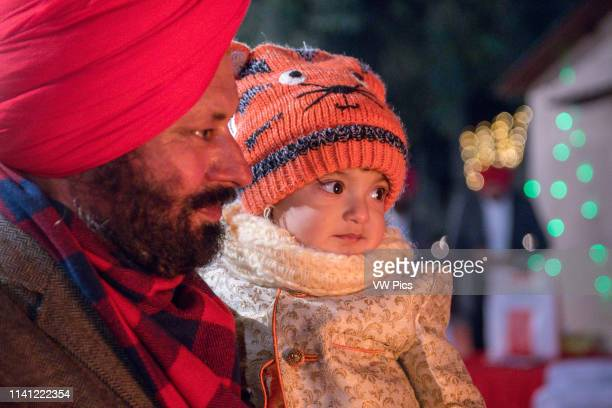 Young child looks into the light of the bonfire at the Lohri celebration in Punjab, India.