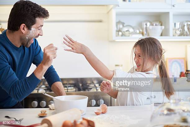 Young child making cake with her father.