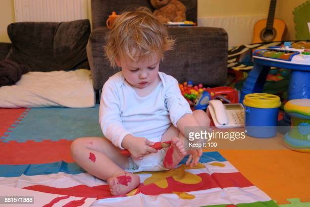 Young child painting their feet