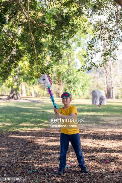 young child playing hit the pinata in a park on a sunny day. - mexican picnic stock pictures, royalty-free photos & images