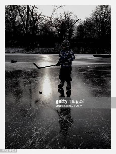 Young child playing ice hockey on frozen lake