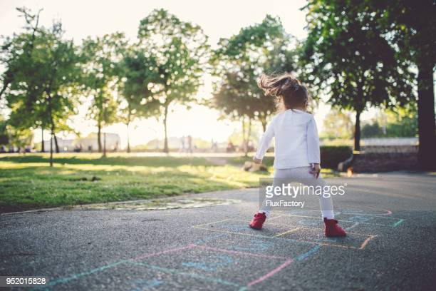 young child playing in the park - hopscotch stock pictures, royalty-free photos & images