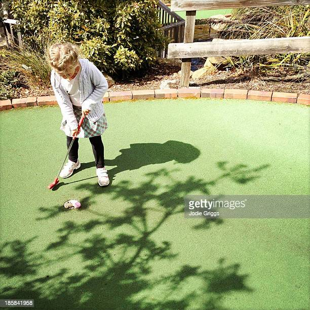 Young child playing mini golf outside