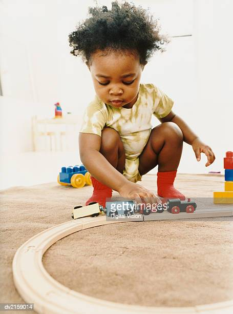 Young Child Playing with a Toy Train