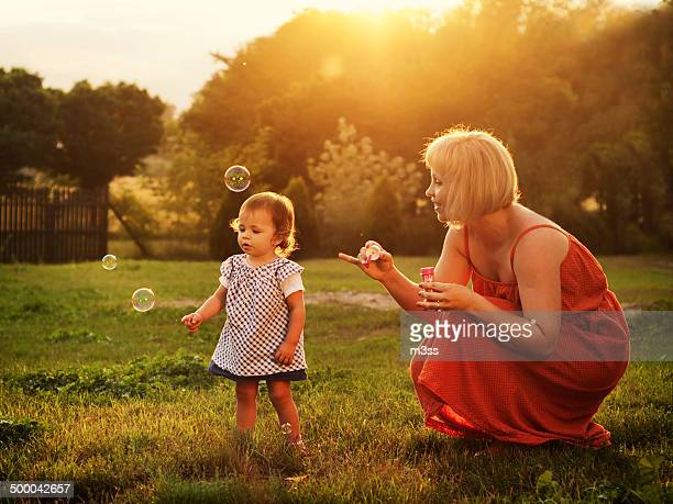 Young child playing with her mother with bubbles