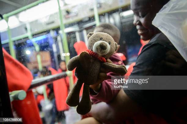 A young child playing with teddy bear inside of the bus to be transferred to a center Malaga