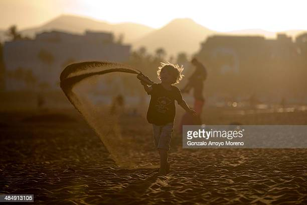A young child plays on the beach at sunset on Puerto del Carmen beach on April 13 2014 in Lanzarote Spain Lanzarote where British Prime Minister...