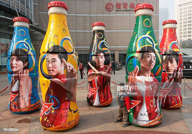 A young child poses for a photo amongst giant CocaCola bottles printed with images of Chinese sports stars during the Coke Bottle Design Contest on...