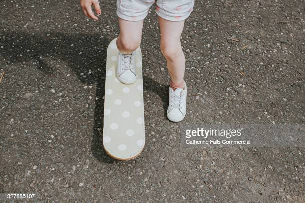 a young child pushes herself along on a spotty skateboard - skate sports footwear stock pictures, royalty-free photos & images