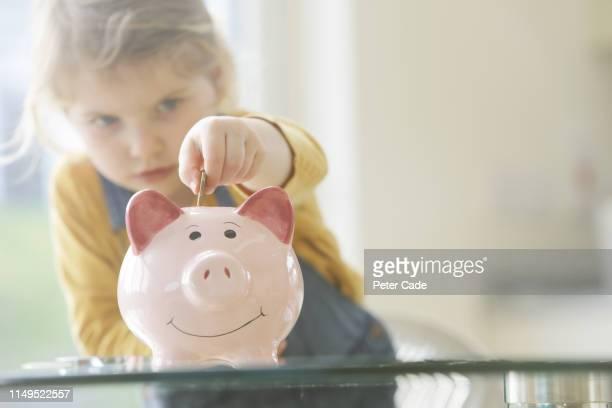 young child putting coins into piggy bank - sparschwein stock-fotos und bilder
