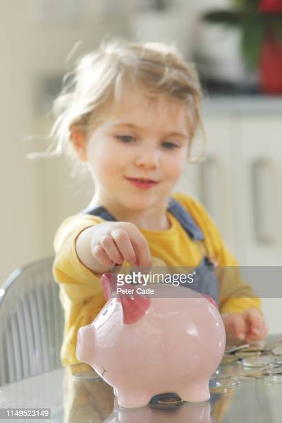 young child putting coins into piggy bank - finance and economy stock pictures, royalty-free photos & images