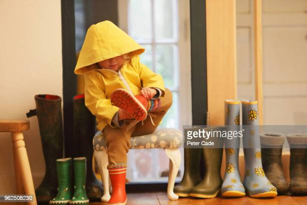 young child putting on wellington boots - footwear stock pictures, royalty-free photos & images
