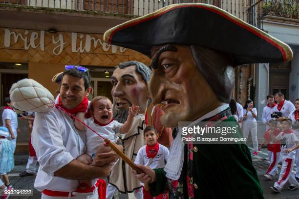 A young child reacts as Caravinagre 'Vinegar face' kiliki hits with his sponge during the Comparsa de Gigantes y Cabezudos or Giants and Big Heads...