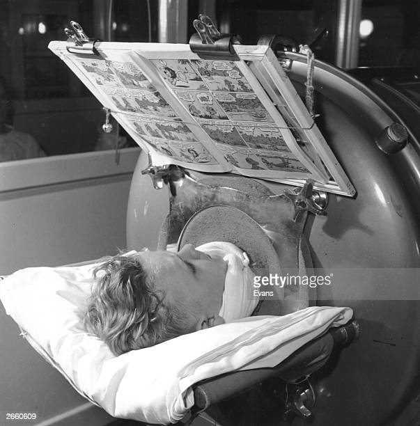 A young child reading a comic while in an iron lung
