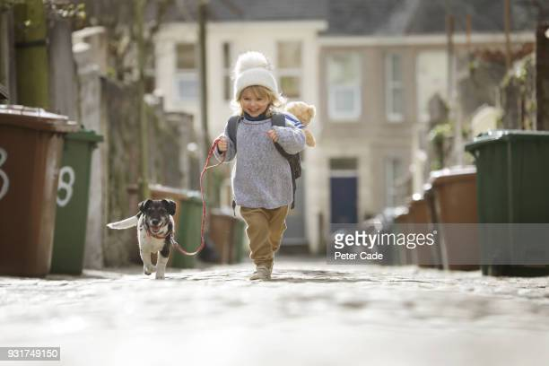 young child running with dog - verantwortung stock-fotos und bilder