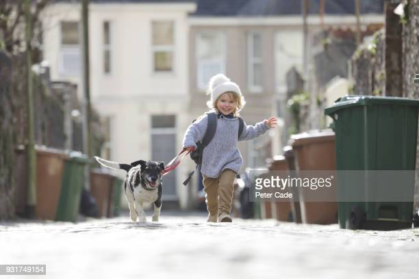 young child running with dog - responsibility stock pictures, royalty-free photos & images