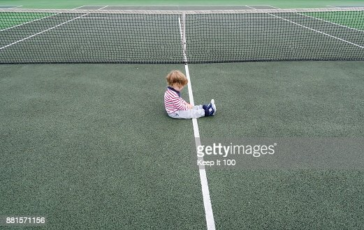 Young child setting on the floor of a tennis court