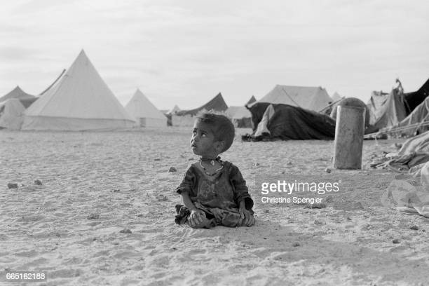 A young child sits alone in a camp in the western Sahara desert. There area has been in territorial dispute between Western Sahara and Morocco since 1976.