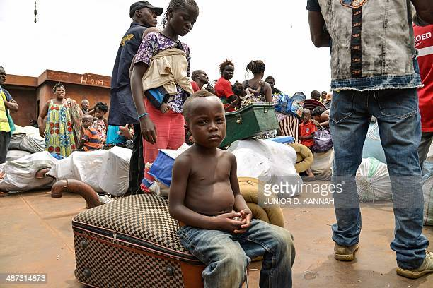 A young child sits on a suitcase as people from the Democratic Republic of Congo arrive on an ATC boat from neighboring Congo Brazzaville after being...