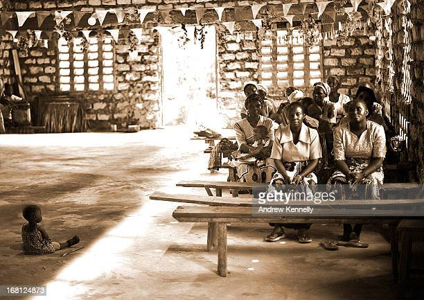 CONTENT] A young child sits on the dirt floor of a church in Kenya