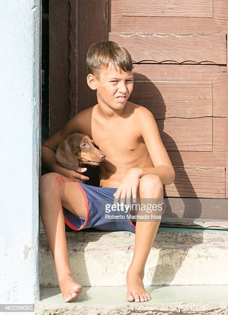 Young child sitting at doorstep shirtless and barefoot with mutt dog pet everyday scene in Cuba
