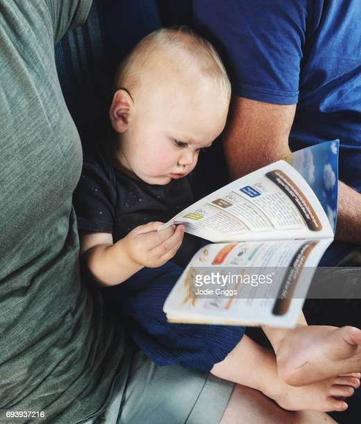 Young child sitting between parents intently reading a brochure written in Chinese