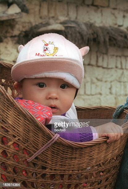 Young child sitting in a basket, Zhongdian, Yunnan province, China. Aug 2003